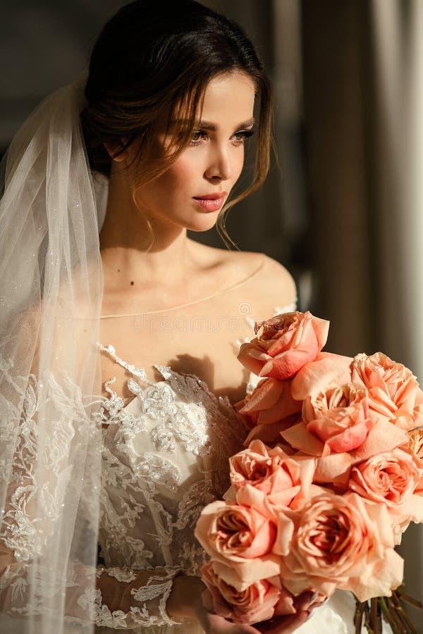 Schöne Braut mit dunklem Haar in elegantem Hochzeitskleid posiert in luxuriösem Interieur lizenzfreie stockbilder