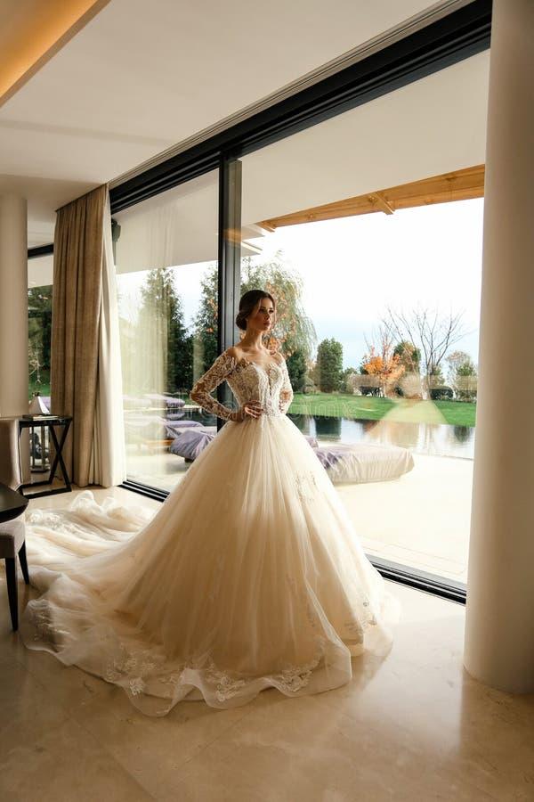 Schöne Braut mit dunklem Haar in elegantem Hochzeitskleid posiert in luxuriösem Interieur lizenzfreies stockfoto