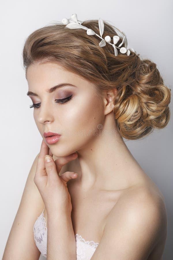 Schöne Braut mit Modehochzeitsfrisur - auf weißem Hintergrund lizenzfreies stockfoto