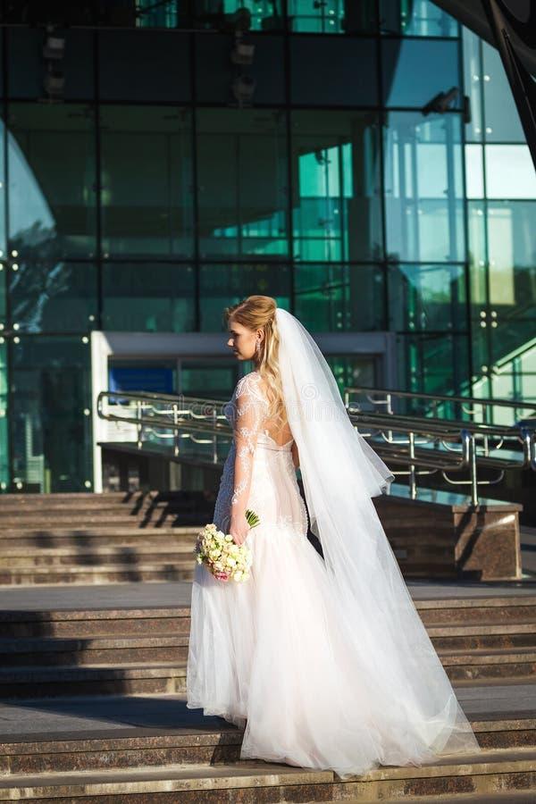 Schöne Braut mit Schleierfliegen auf dem Wind, der oben anhebt stockfoto