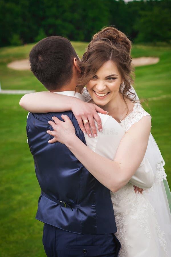 Schöne Braut und Bräutigam, die in der Natur lächelt und umarmt lizenzfreies stockbild