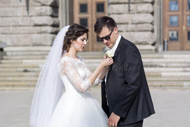 Schöne Braut und Bräutigam, die für die Hochzeit im Freien sich vorbereitet lizenzfreies stockbild