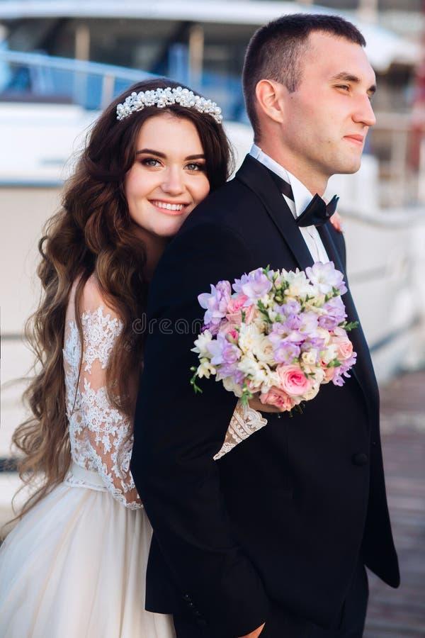 Schöne Braut und Bräutigam, die nahe Seeyacht umarmt lizenzfreies stockbild