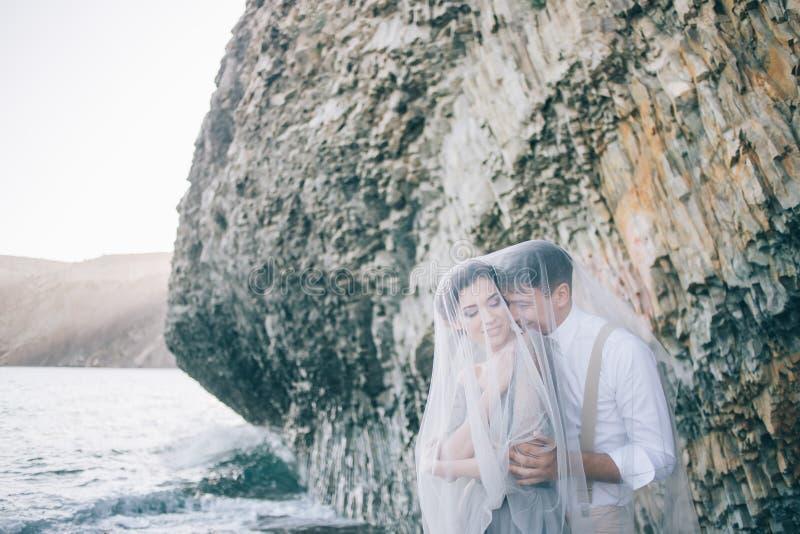 Schöne Braut und Bräutigam unter einem Schleier nahe dem Meer, sprechend und lächelt stockfoto
