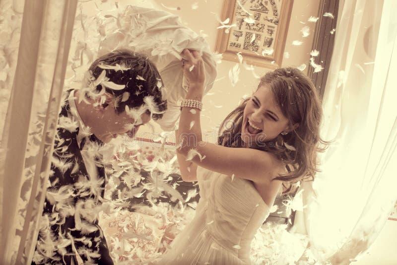 Schöne Braut und der Bräutigam, die mit Federkissenschlacht spielt, betten Hochzeitstag lizenzfreies stockbild