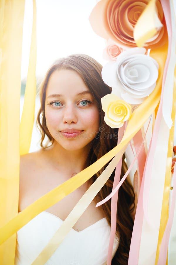 Schöne Braut unter Papierblumendekoration lizenzfreie stockfotografie