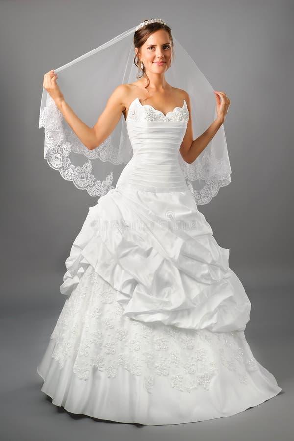 Schöne Braut unter Schleier im Hochzeitskleid stockbilder