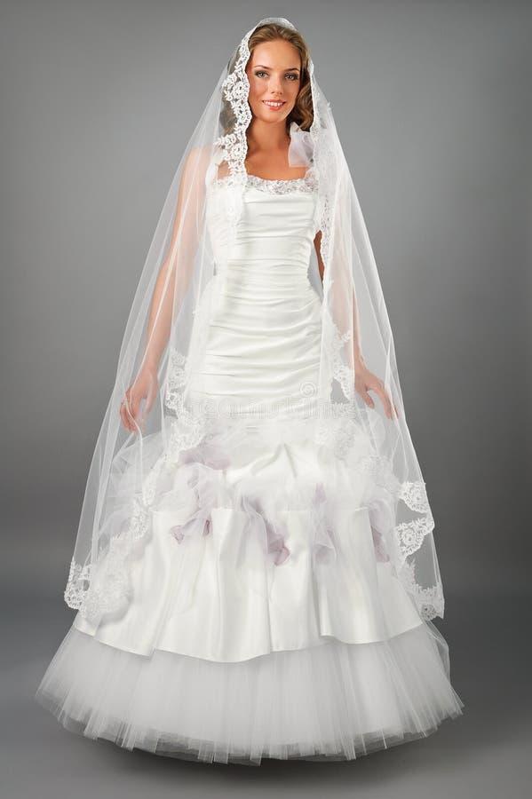 Schöne Braut unter tragendem Hochzeitskleid des Schleiers lizenzfreie stockfotos