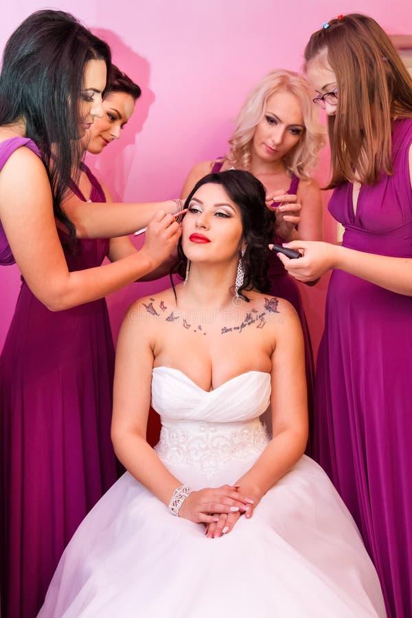 Schöne Braut zusammen mit 4 Brautjungfern in den violetten ähnlichen Kleidern stockfoto