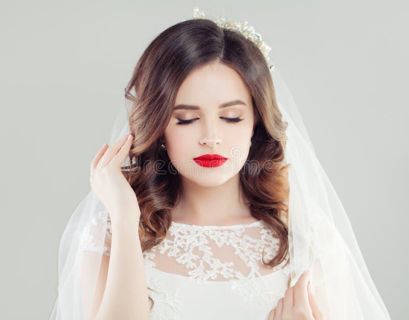 Schöne Brautfrau mit rotem Lippenmake-up, dem Brauthaar und Schleier stockfotos