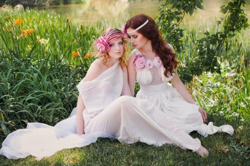 Schöne Brautjungfer, die in der Natur sitzt stockfoto