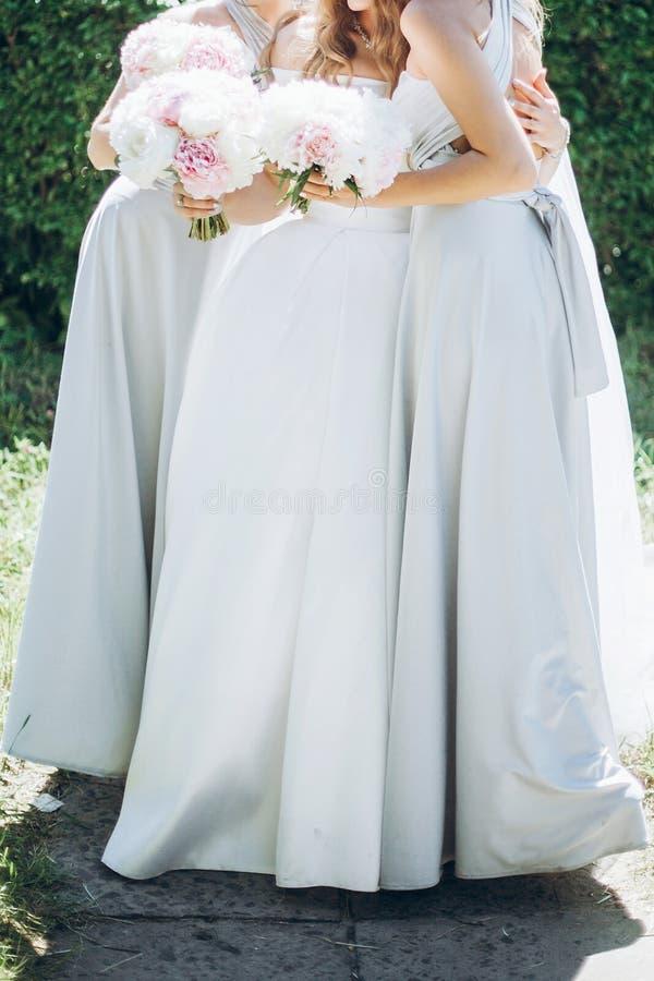 Schöne Brautjungfern und Braut, die stilvolle Pfingstrosenblumensträuße hält stockfotografie