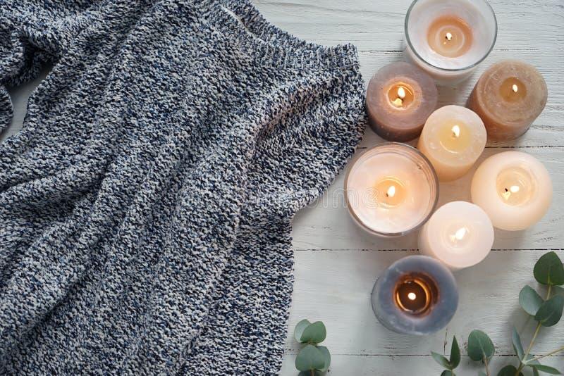 Schöne brennende Kerzen mit warmer Strickjacke auf weißem Holztisch stockfotografie