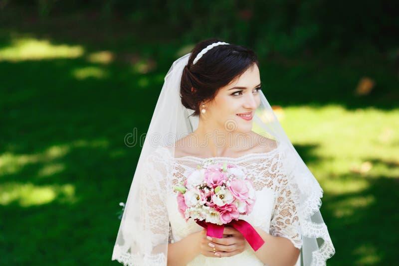 Schöne brunette Braut mit dem Blumenstrauß im Freien Glückliche Braut übertreffen stockfotos