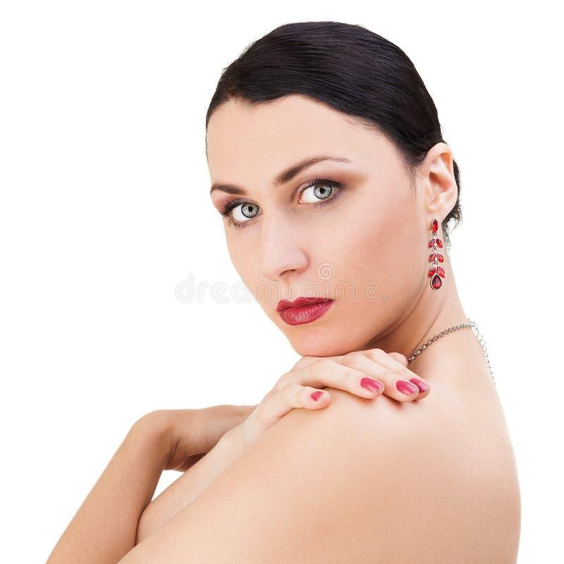 Schöne Brunette-Frau, die über ihrer Schulter schaut lizenzfreie stockfotos