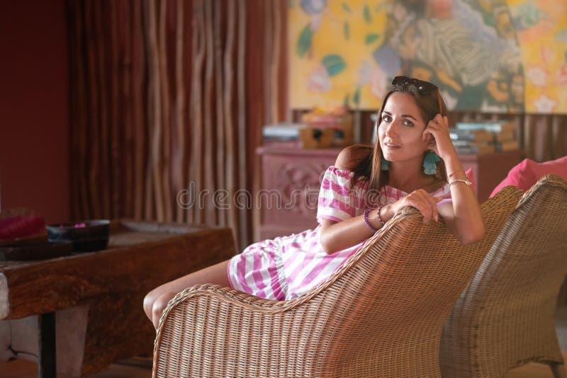 Sch?ne brunette Frau, die in einem Stuhl zur H?lfte Drehung sitzt Innen in der ethnischen Art Abschluss oben lizenzfreies stockbild