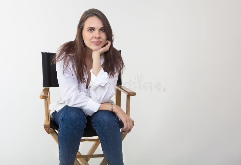 Sch?ne brunette Frau, die am Studio im wei?en Hemd aufwirft stockbilder