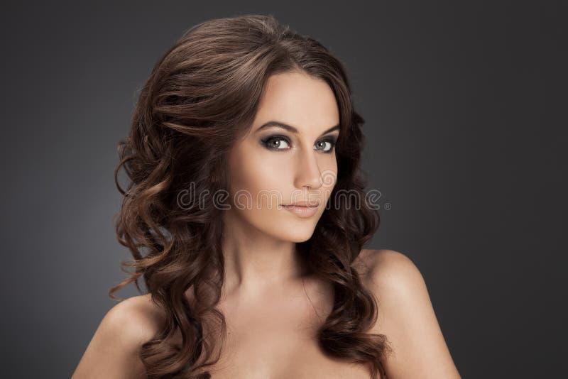 Schöne Brunette-Frau. Gelocktes langes Haar. stockfoto