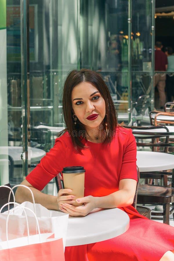 Schöne brunette Frau in rotes Kleidertrinkendem Kaffee in einer Kaffeestube stockbilder