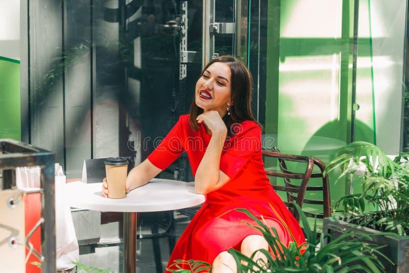 Schöne brunette Frau in rotes Kleidertrinkendem Kaffee in einer Kaffeestube lizenzfreies stockbild