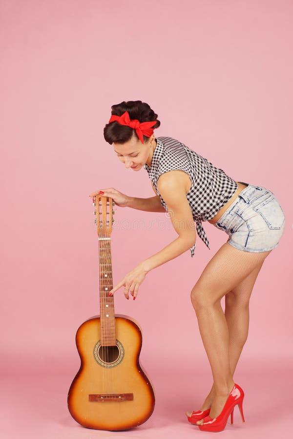 Schöne brunette Frau steht und hält eine Gitarre durch den Fingerboard, versucht, die Schnüre zu berühren, lernt, Stift-obenart a lizenzfreie stockbilder