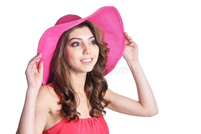 Schöne brunette junge Frau, die im rosa Hut lokalisiert auf weißem Hintergrund aufwirft lizenzfreie stockfotografie