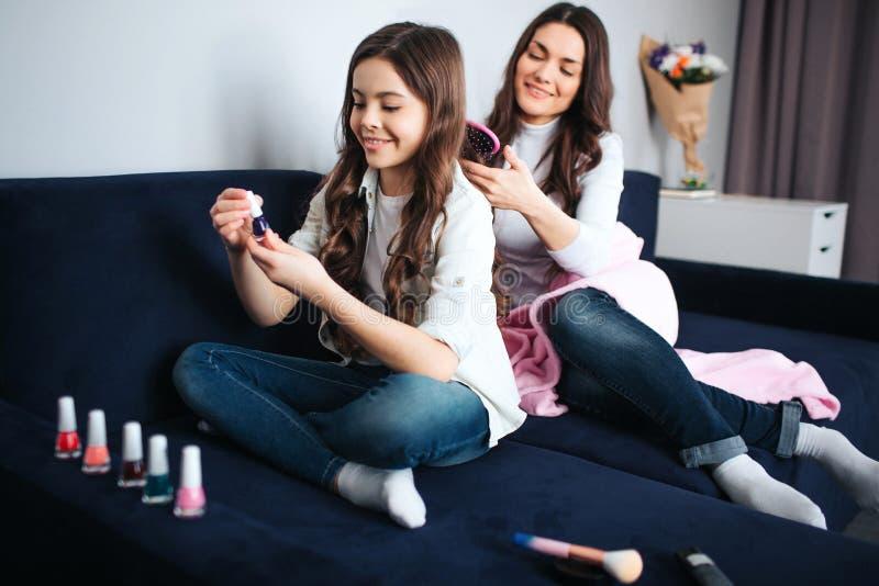 Schöne brunette kaukasische Mutter und Tochter sitzen zusammen im Raum MädchengebrauchsNagellack und Lächeln Bürste der jungen Fr lizenzfreie stockfotografie