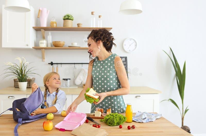 Schöne brunette Mutter und ihre Tochter, die das gesunde Mittagessen verpackt und Schultasche vorbereitet stockfotos