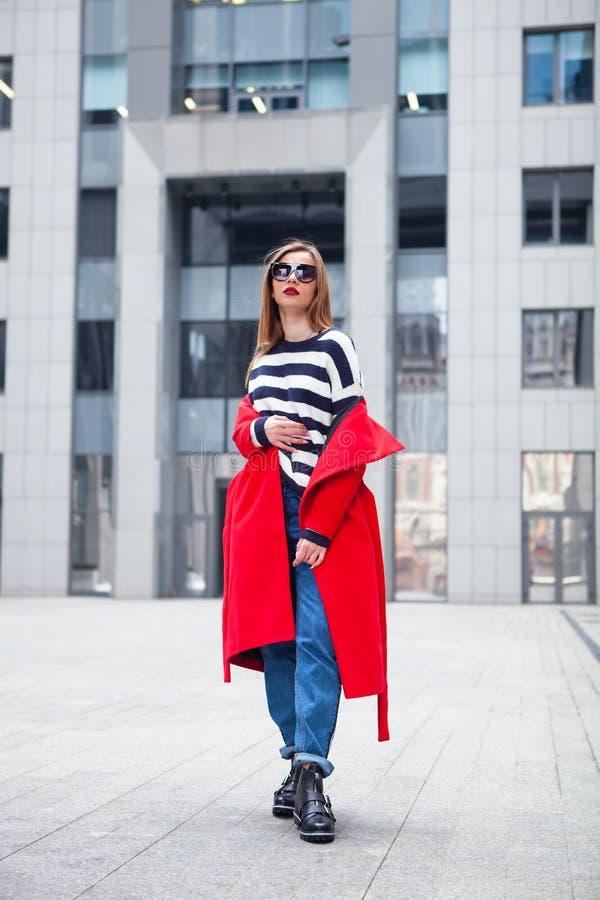 Schöne Brunetteaufstellung im Freien roter Mantel, gestreifter Pullover, Jeans und Modesonnenbrille Helle rote Lippen stockbilder