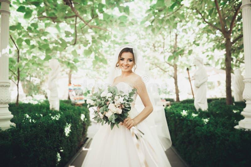 Schöne Brunettebraut im eleganten weißen Kleid, das den Blumenstrauß aufwirft ordentliche Bäume hält stockfotos