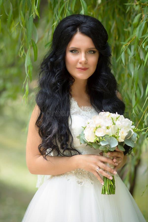 Schöne Brunettebraut mit einem Hochzeitsblumenstrauß, der im Park aufwirft stockbilder