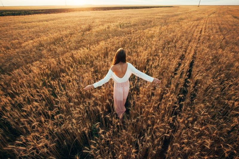 Schöne Brunettedame auf dem Weizengebiet bei Sonnenuntergang lizenzfreies stockfoto
