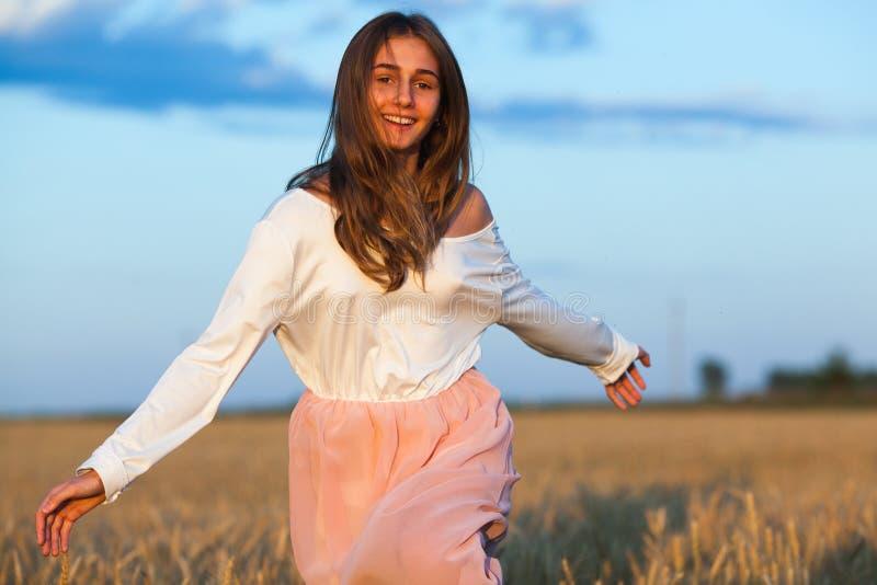 Schöne Brunettedame auf dem Weizengebiet bei Sonnenuntergang lizenzfreie stockfotos