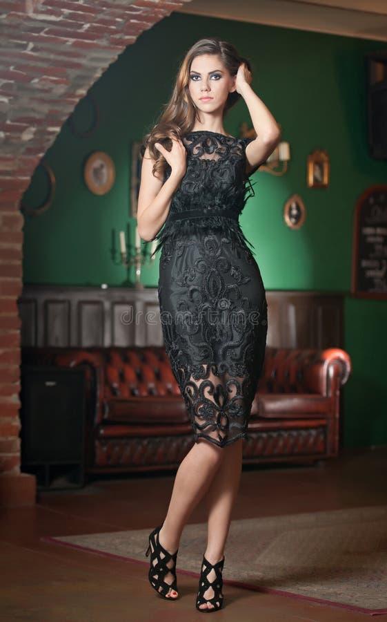 Schöne Brunettedame im eleganten schwarzen Spitzekleid, das in einer Weinleseszene aufwirft stockfotografie