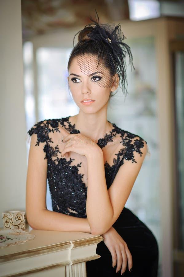 Schöne Brunettedame im eleganten schwarzen Spitzekleid, das in einer Weinleseszene aufwirft Junge sinnliche moderne Frau lizenzfreie stockfotografie
