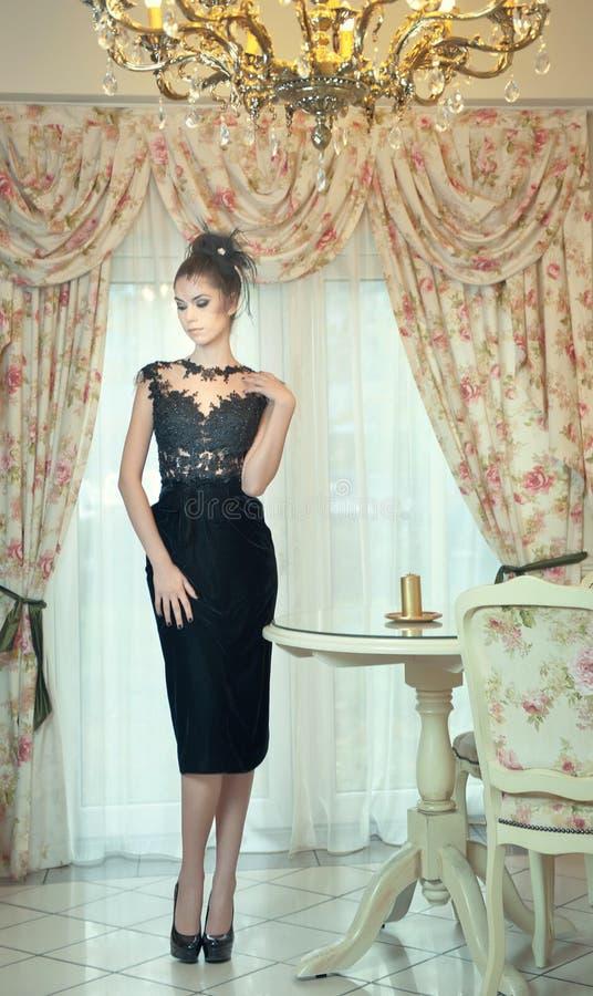 Schöne Brunettedame im eleganten schwarzen Spitzekleid, das in einer Weinleseszene aufwirft Junge sinnliche moderne Frau auf hohe stockbilder