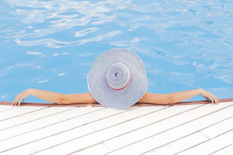 Schöne Brunettefrau auf dem Strand allein, der in einem Hut sich entspannt S lizenzfreie stockbilder