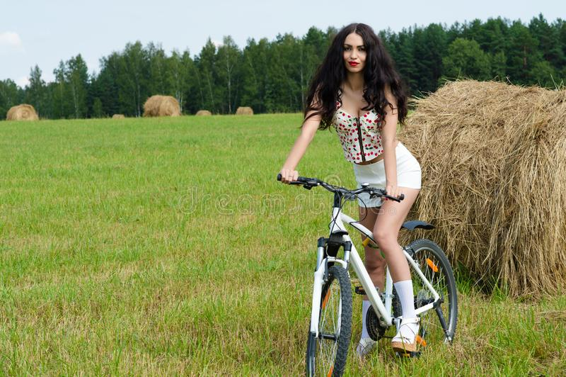 Schöne Brunettefrau auf Fahrrad auf dem Gebiet lizenzfreie stockbilder