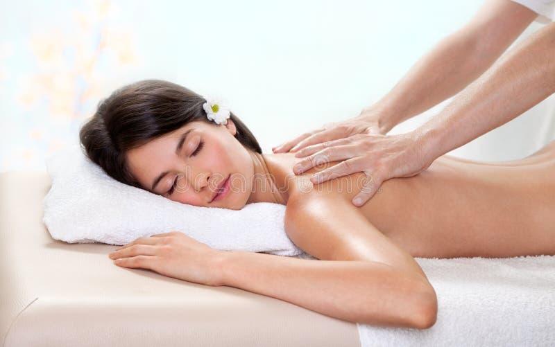Schöne Brunettefrau, die eine rückseitige Massage erhält stockfoto