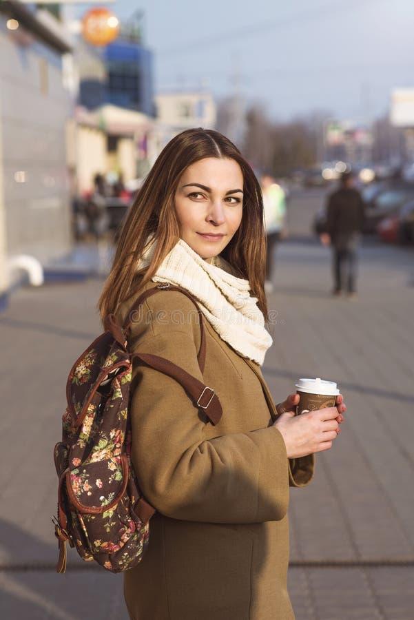 Schöne Brunettefrau, die eine Tasche und eine Schale heißen Tee oder Kaffee, stehend in der Straße hält stockfoto