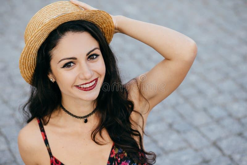 Schöne Brunettefrau, die ihre weißen perfekten Zähne tragen den Strohhut und Anhänger demonstrierend haben gute Laune beim Haben  stockbild