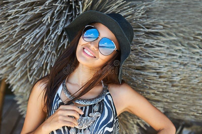 Schöne Brunettefrau, die am sonnigen Sommertagesabschluß herauf por aufwirft stockbild
