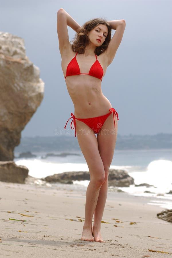 Schöne Brunettefrau, die am Strand im roten Bikini aufwirft stockfotos