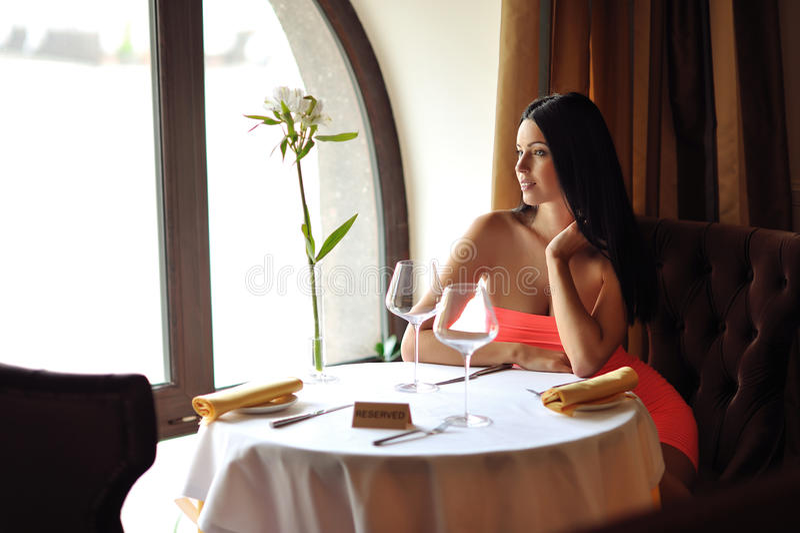 Schöne Brunettefrau, die am Tisch im Restaurant wartet lizenzfreies stockbild