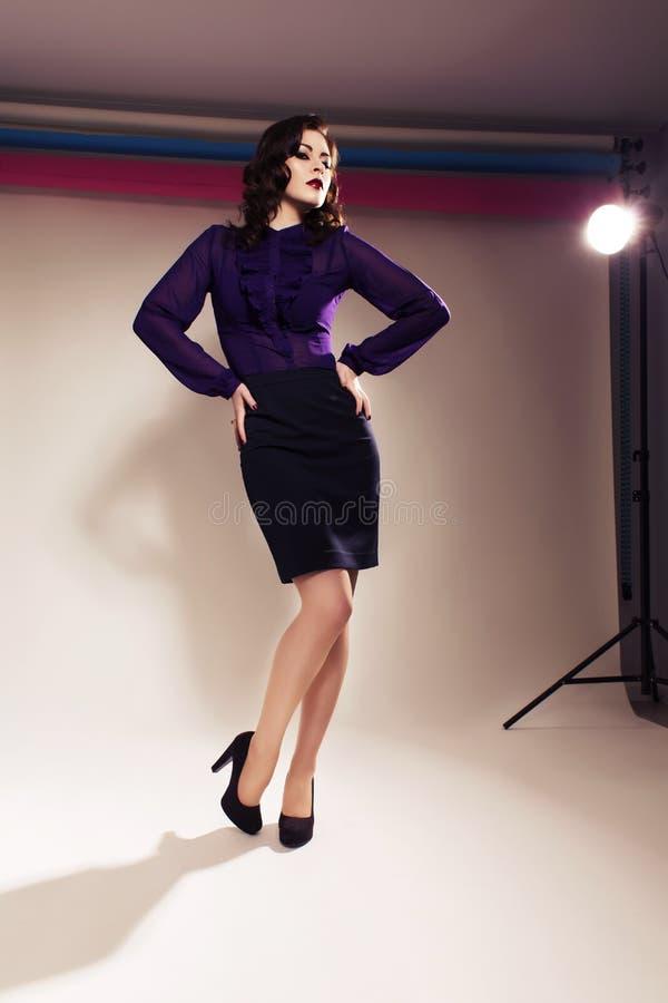 Schöne Brunettefrau im dunklen Rock und in der Bluse mit der Glättung von m lizenzfreie stockfotografie