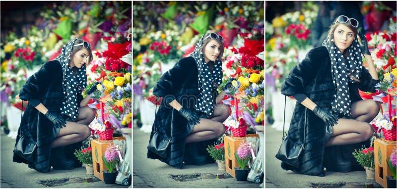 Schöne Brunettefrau im Schwarzen am Blumengeschäft lizenzfreie stockfotos