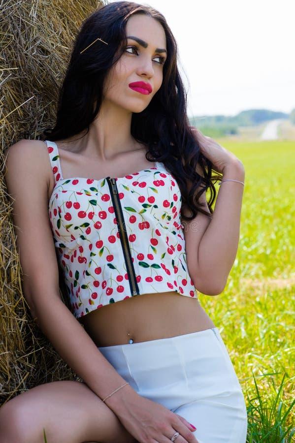 Schöne Brunettefrau im Sommer am Heuschober stockfoto