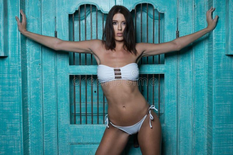 Schöne Brunettefrau im weißen Bikini lizenzfreies stockfoto