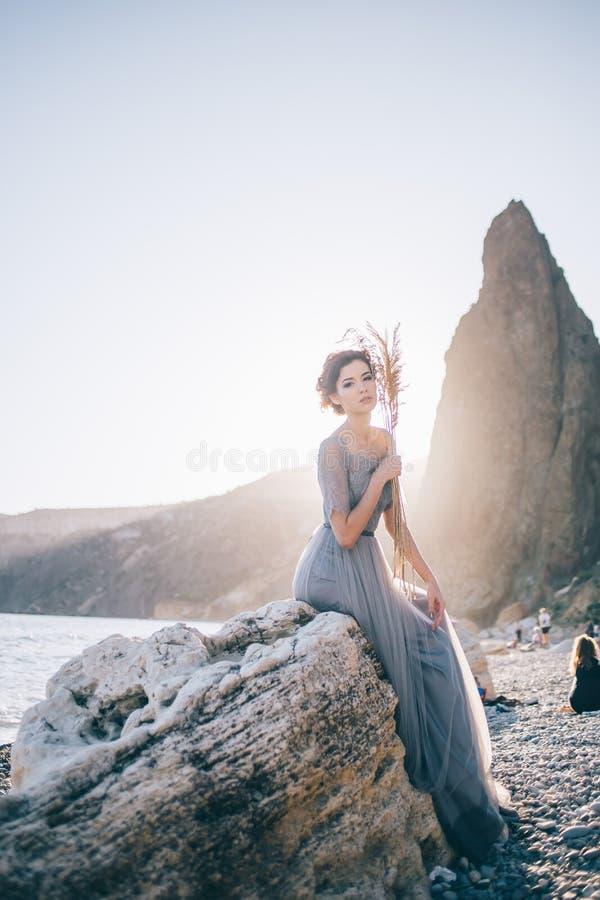 Schöne Brunettefrau in langes Kleidersitzendem weißem Stein durch das Meer bei Sonnenuntergang und das Betrachten der Kamera stockfoto