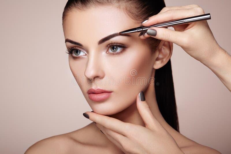 Schöne Brunettefrau malt die Augenbrauen lizenzfreies stockbild